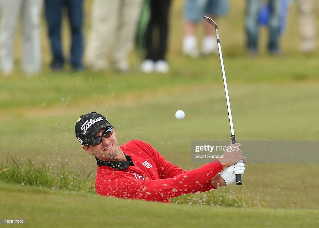 Adam Scott of Australia plays out of a bunker on the 1st hole during round one of the 2013 Australian Masters at Royal Melbourne Golf Course on November 14, 2013 in Melbourne, Australia.