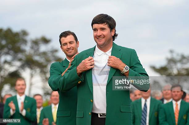 Adam Scott of Australia presents Bubba Watson of the United States with the green jacket after Watson won the 2014 Masters Tournament by a...