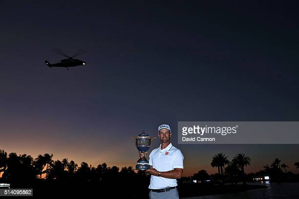 Adam Scott of Australia proudly holds the trophy as Donald Trump takes off in his helicopter after his one shot win in the final round of the 2016...