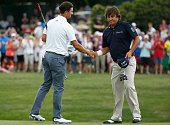Adam Scott of Australia shakes hands with Jason Dufner after a birdie putt on the third playoff hole to defeat him and win the 18th hole during the...