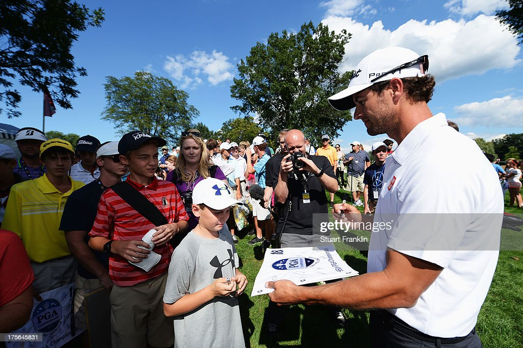 Adam Scott of Australia signs his autograph for a fan during the Mercedes Benz Hole in One Challenge prior to the start of the 95th PGA Championship at Oak Hill Country Club on August 5, 2013 in Rochester, New York.