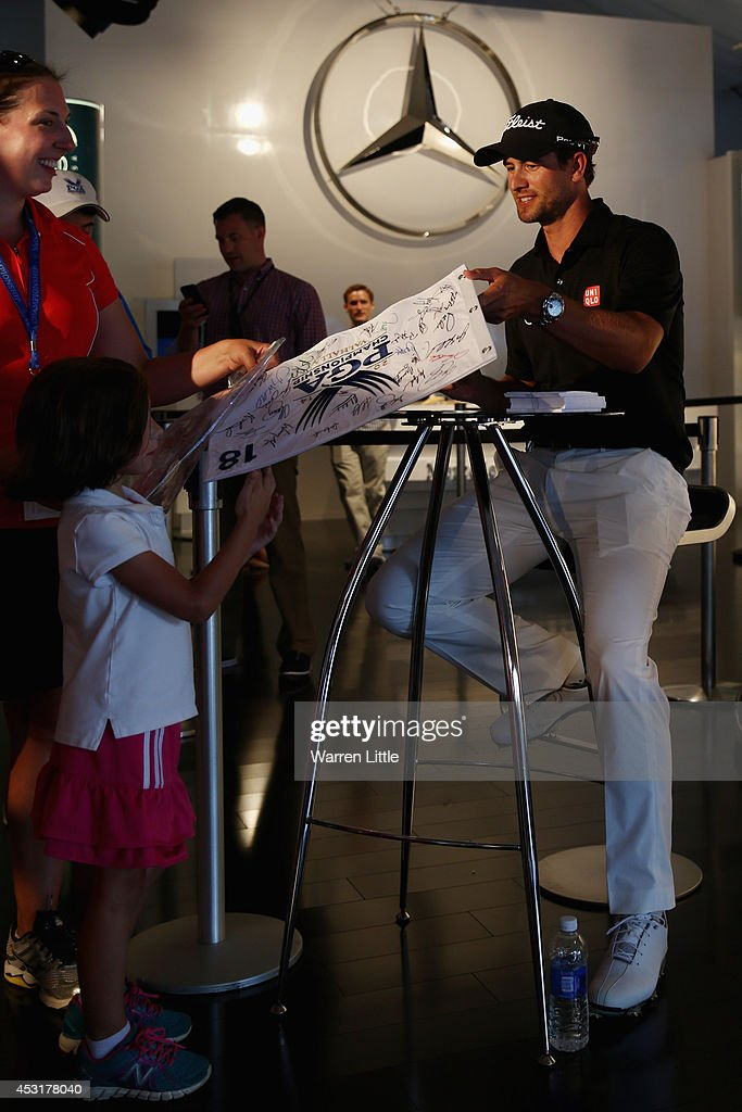 Adam Scott of Australia signs his autograph for a fan in the Mercedes Benz Performance Centre during a practice round prior to the start of the 96th PGA Championship at Valhalla Golf Club on August 4, 2014 in Louisville, Kentucky.