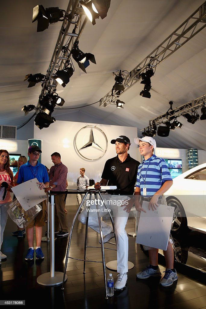 Adam Scott of Australia smiles for a photo after signing his autograph for a fan in the Mercedes Benz Performance Centre during a practice round prior to the start of the 96th PGA Championship at Valhalla Golf Club on August 4, 2014 in Louisville, Kentucky.