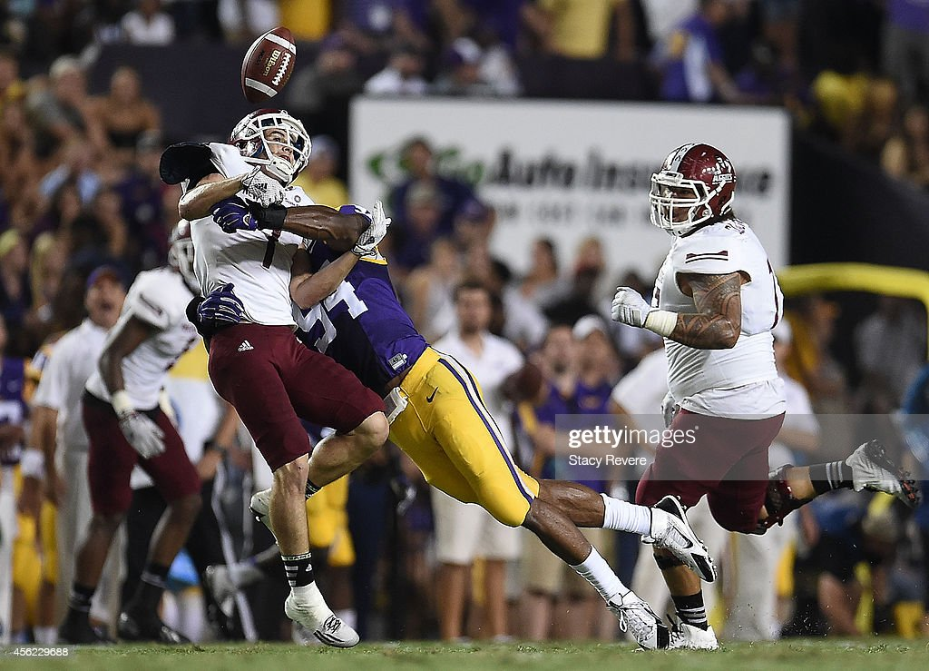 Adam Shapiro of the New Mexico State Aggies looses the ball while being hit by Danielle Hunter of the LSU Tigers during the first quarter of a game...
