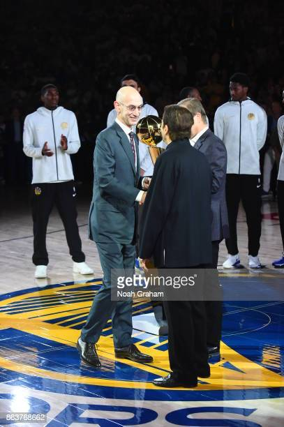 Adam Silver congratulates Warriors owner Peter Guber of the Golden State Warriors during the NBA Championship ring ceremony for the Golden State...
