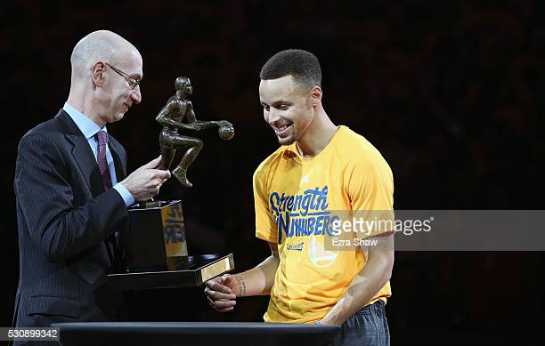 Adam Silver the Commissioner of the NBA gives the MVP Award to Stephen Curry of the Golden State Warriors before their game against the Portland...