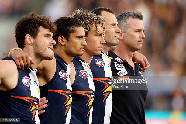 Adam Simpson coach of the Eagles looks on with his players for the national anthem during the AFL Second Preliminary Final match between the West...