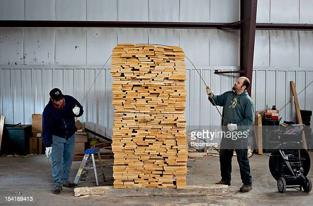 Adam Spencer lumber inspector right and employee Patrick Cassidy band a stack of basswood lumber as it is prepared for overseas shipment at the...