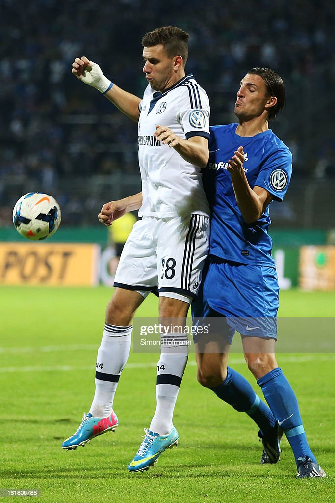 <a gi-track='captionPersonalityLinkClicked' href=/galleries/search?phrase=Adam+Szalai&family=editorial&specificpeople=2344504 ng-click='$event.stopPropagation()'>Adam Szalai</a> of Schalke is challenged by Benjamin Gorka of Darmstadt during the DFB Cup second round match between Darmstadt 98 and Schalke 04 at Stadion am Boellenfalltor on September 25, 2013 in Darmstadt, Germany.