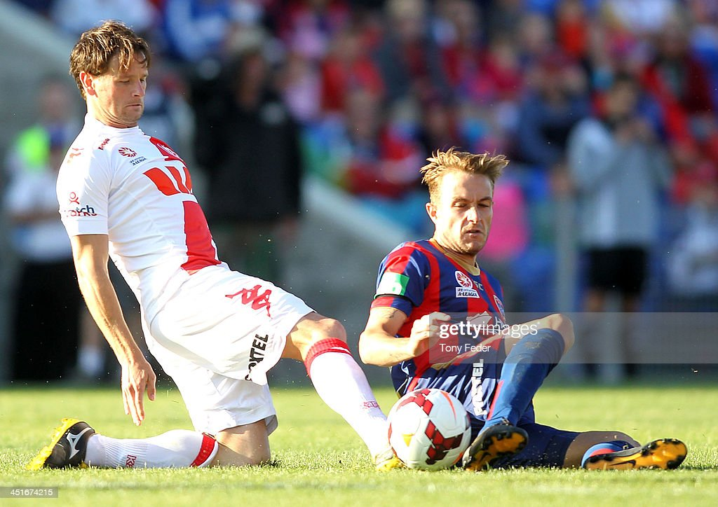 Adam Taggart of the Jets attempts to kick the ball away from his Heart opponent during the round seven A-League match between the Newcastle Jets and the Melbourne Heart at Hunter Stadium on November 24, 2013 in Newcastle, Australia.