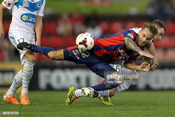 Adam Taggart of the Jets contests the ball with Leigh Broxham of the Victory during the round 26 ALeague match between the Newcastle Jets and...