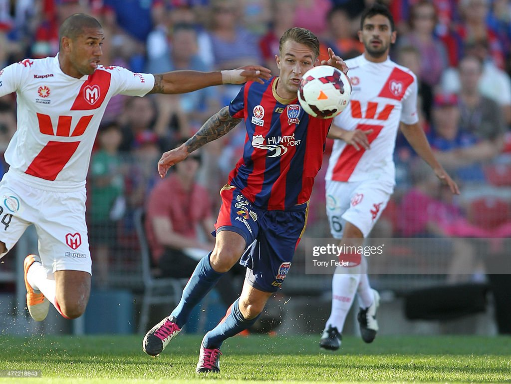 Adam Taggart of the Jets contests the ball with Patrick Kisnorbo of the Heart during the round 22 A-League match between the Newcastle Jets and Melbourne Heart at Hunter Stadium on March 8, 2014 in Newcastle, Australia.