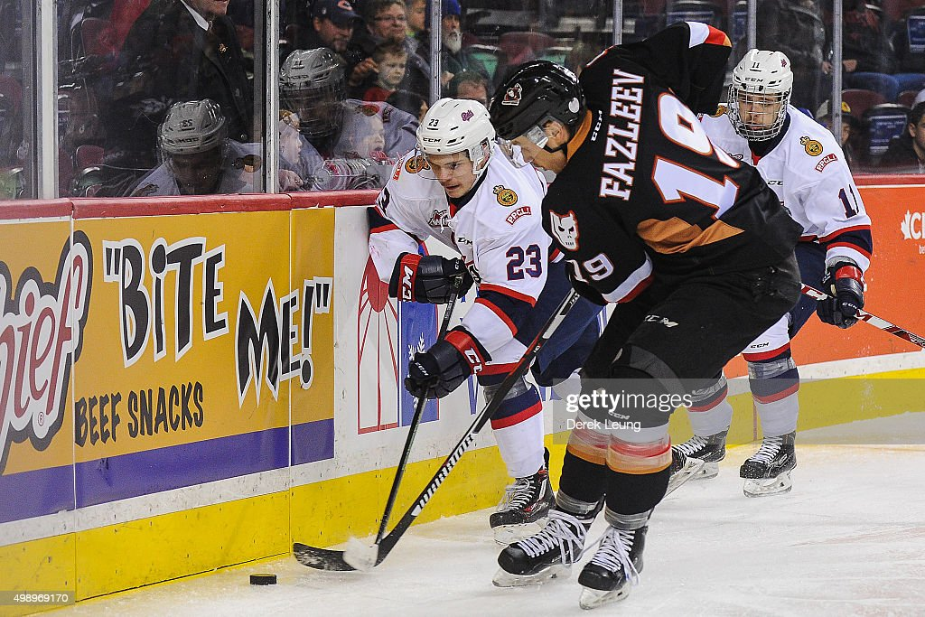 Adam Tambellini #19 of the Calgary Hitmen looks to check Sam Steel #23 of the Regina Pats during a WHL game at Scotiabank Saddledome on November 27, 2015 in Calgary, Alberta, Canada.