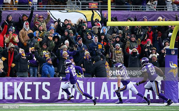 Adam Thielen of the Minnesota Vikings picks up a blocked punt for a touchdown against the Carolina Panthers in the first quarter on November 30 2014...