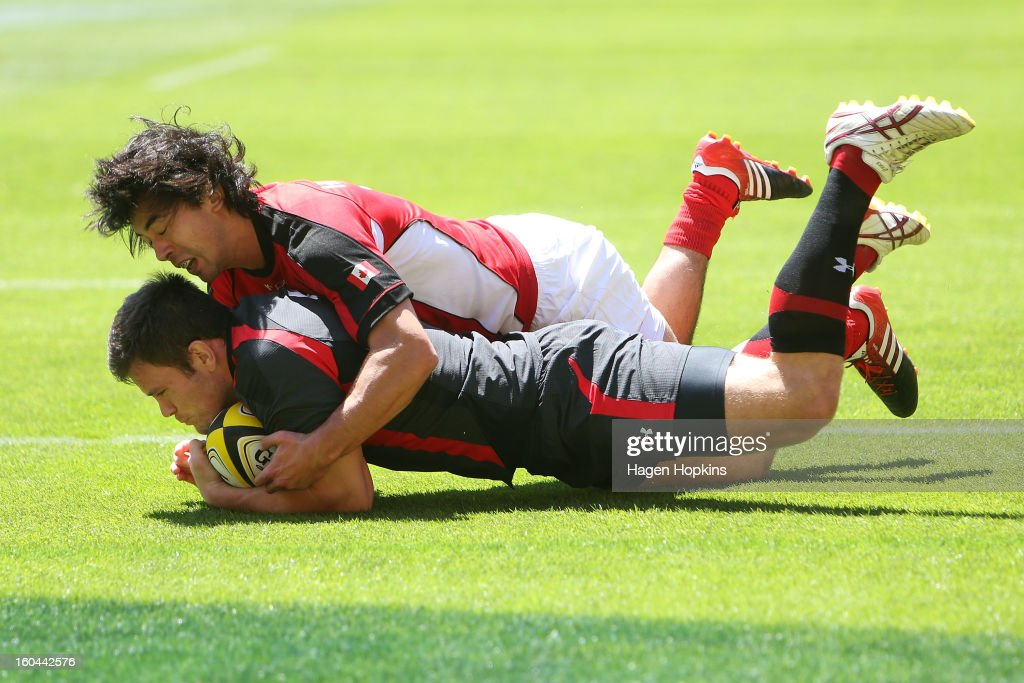 Adam Thomas of Wales scores a try in the tackle of Nathan Hirayama of Canada during the 2013 Wellington Sevens at Westpac Stadium on February 1, 2013 in Wellington, New Zealand.
