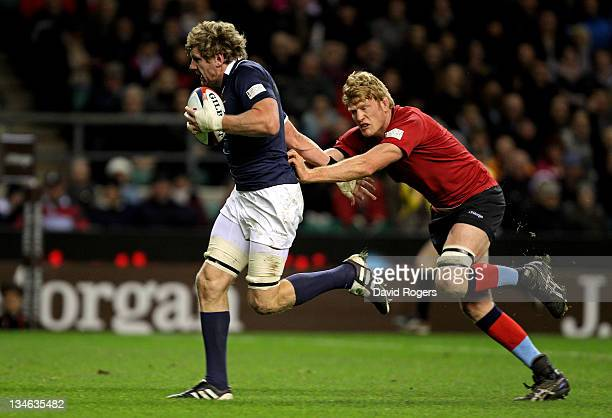 Adam Thomson of the Southern Hemisphere XV goes through the tackle from Hugh Vyvyan of the H4H Northern Hemisphere XV during the Help For Heroes...
