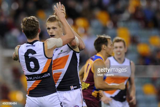 Adam Treloar of the Giants celebrates kicking a goal with Lachie Whitfield during the round 13 AFL match between the Brisbane Lions and the Greater...
