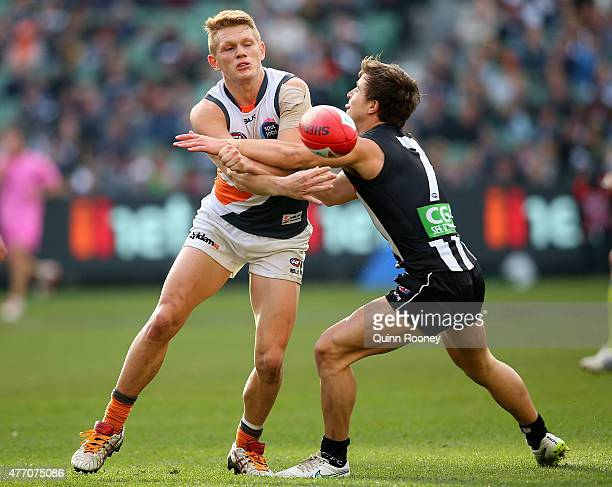 Adam Treloar of the Giants handballs whilst being tackled by Ben Kennedy of the Magpies during the round 11 AFL match between the Collingwood Magpies...