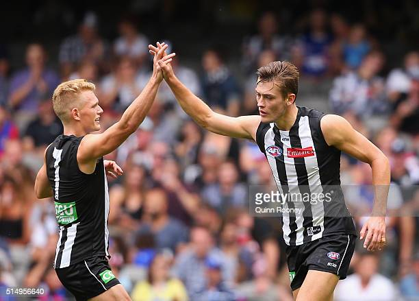 Adam Treloar of the Magpies congratulates Darcy Moore after he kickied a goal during the 2016 NAB Challenge AFL match between the Collingwood Magpies...