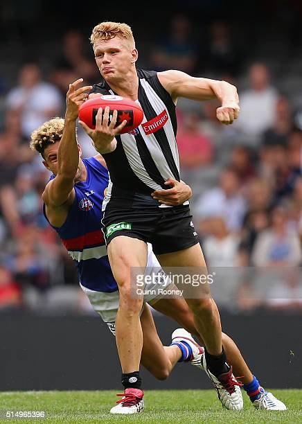 Adam Treloar of the Magpies handballs whilst being tackled by Jason Johannisen of the Bulldogs during the 2016 NAB Challenge AFL match between the...