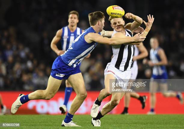 Adam Treloar of the Magpies handballs whilst being tackled by Sam Durdin of the Kangaroos during the round 20 AFL match between the North Melbourne...