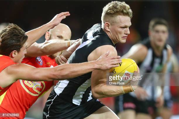 Adam Treloar of the Magpies runs the ball during the round 17 AFL match between the Gold Coast Suns and the Collingwood Magpies at Metricon Stadium...