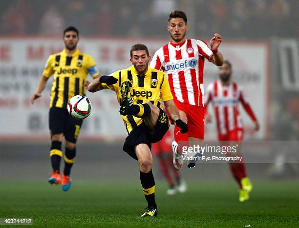 Adam Tzanetopoulos of AEK passes the ball defended by Dimitris Diamantakos of Olympiacos during the Greek Cup match between Olympiacos Piraeus and...