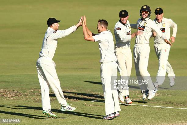 Adam Voges and Jason Behrendorff of Western Australia celebrate the wicket of Trent Copeland of New South Wales during the Sheffield Shield match...