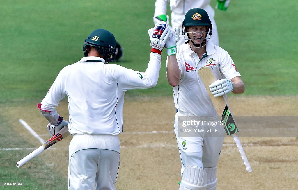 Adam Voges (R) of Australia celebrates 200 runs with team mate Nathan Lyon (L) during day three of the first cricket Test match between New Zealand and Australia at the Basin Reserve in Wellington on February 14, 2016. / AFP / Marty Melville