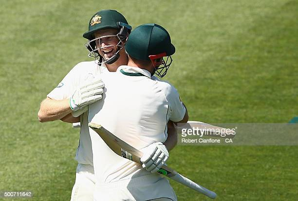 Adam Voges of Australia celebrates with Shaun Marsh after reaching his century during day one of the First Test match between Australia and the West...