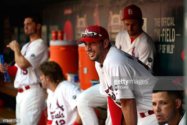 Adam Wainwright of the St Louis Cardinals sits in the dugout with teammates during the sixth inning against the San Diego Padres at Busch Stadium on...