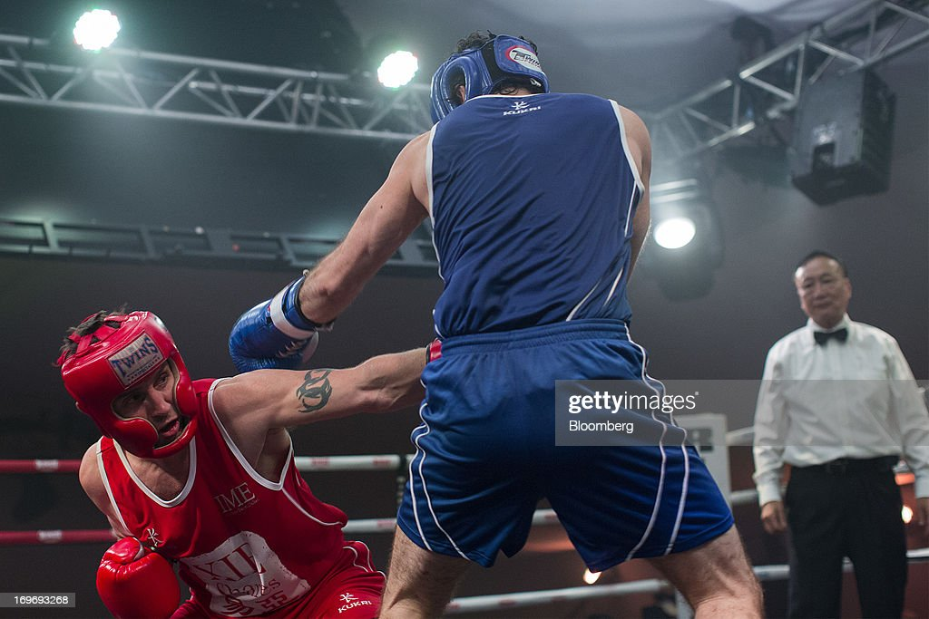 Adam Wallace, chief operating officer of Factorial Management Ltd., in red, exchanges blows with Darryl Ricklow, a broker at Louis Capital Markets HK Ltd., in the third bout during the Hedge Fund Fight Nite 2013 charity fighting event in Hong Kong, China, on Thursday, May 30, 2013. The event raises money for Operation Breakthrough and Operation Smile charities. Photographer: Jerome Favre/Bloomberg via Getty Images
