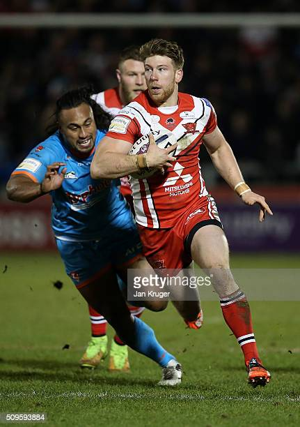 Adam Walne of Salford Red Devils breaks through the tackle of Atelea Vea of St Helens during the First Utility Super League match between Salford...