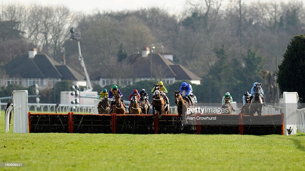 Adam Wedge riding Islandmagee (C, blue) clear the last to win the kempton.co.uk Conditional Jockeys' Handicap Hurdle Race at Kempton racecourse on February 08, 2013 in Sunbury, England.