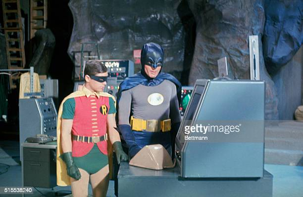 Adam West at 'Batman' and Bert Ward as 'Robin' stand near the 'Batmobile' during filming on an episode from the Batman television series