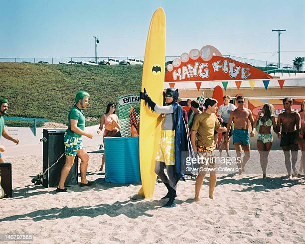 Adam West US actor wearing a pair of yellow and white long shorts over his costume and standing on a beach with a yellow surfboard with the Batman...