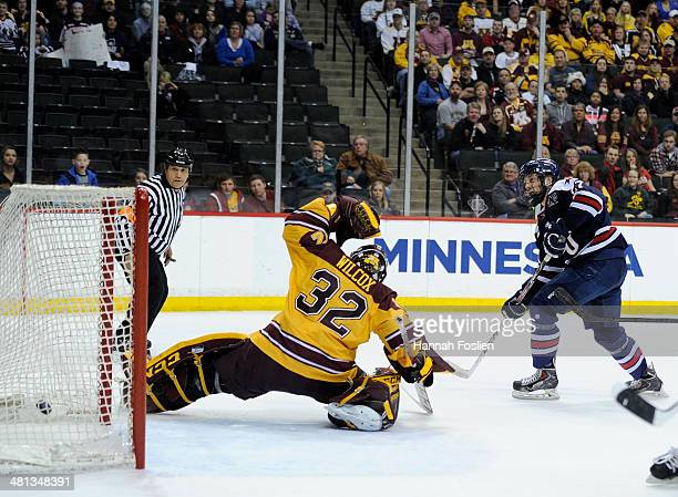 Adam Wilcox of the Minnesota Golden Gophers defends the net as a shot by Zac Lynch of the Robert Morris Colonials gets past him during the second...