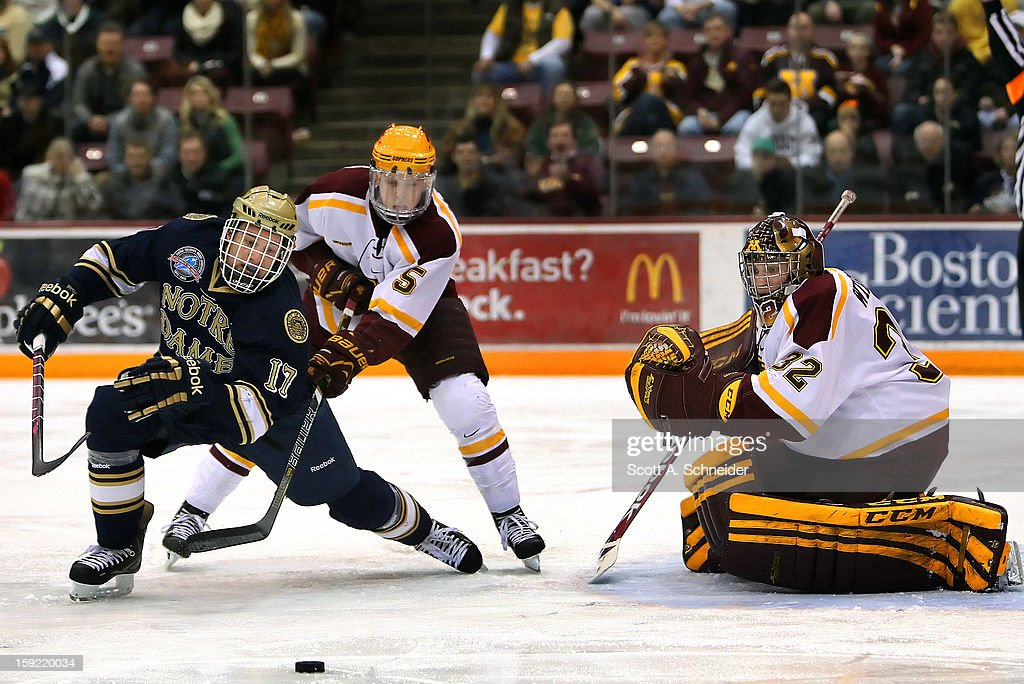 Adam Wilcox #32 of the Minnesota Gophers watches teammate <a gi-track='captionPersonalityLinkClicked' href=/galleries/search?phrase=Mike+Reilly+-+Jugador+de+hockey+sobre+hielo&family=editorial&specificpeople=12893936 ng-click='$event.stopPropagation()'>Mike Reilly</a> #5 and Nick Larson #5 of the Notre Dame Fighting Irish chase a loose puck January 8, 2013 at Mariucci Arena in Minneapolis, Minnesota.