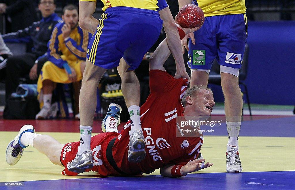 Adam Wisniewski of Poland vies with Jonas Larholm (L) and Niclas Ekberg (R) of Sweden, during the Men's European Handball Championship 2012 group 1 match between Poland and Sweden at Belgrade Arena Hall on January 21, 2011 in Belgrade, Serbia.