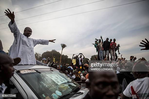 TOPSHOT Adama Barrow the flagbearer of the coalition of the seven opposition political parties in Gambia greets supporters from the roof of his car...