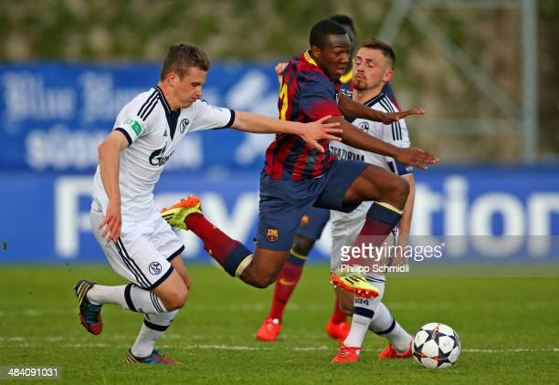 Adama Traore of FC Barcelona competes for the ball with Miles Mueller and Pascal Itter of FC Schalke 04 during the UEFA Youth League Semi Final match...