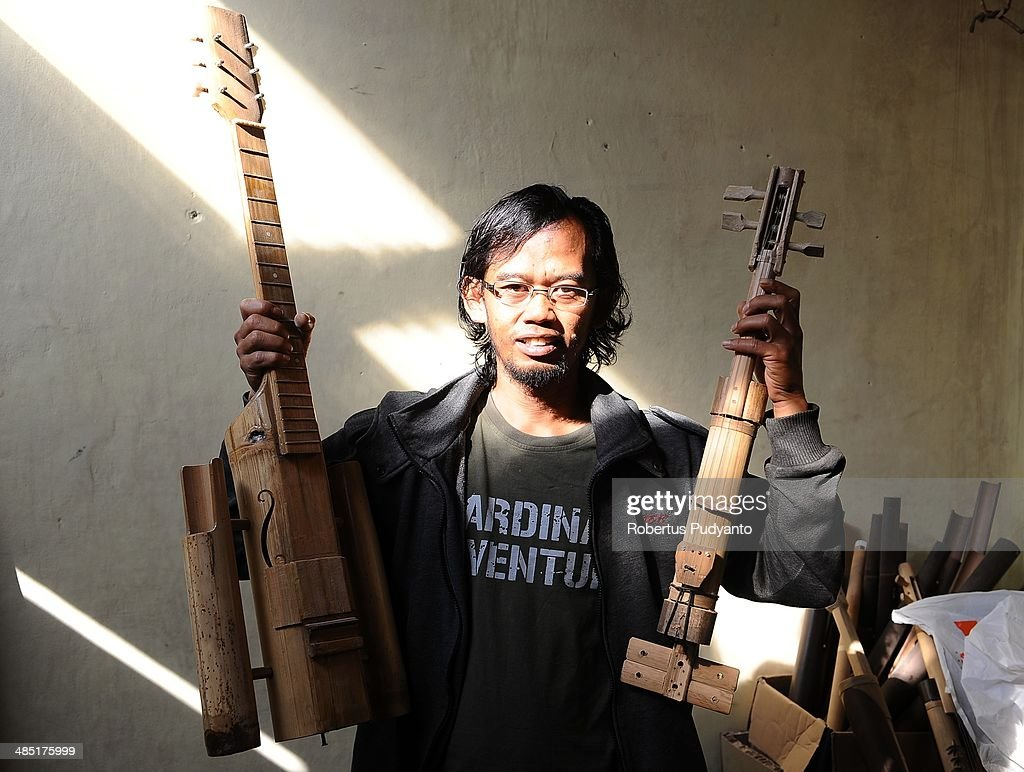 Adang Muhidin, founder of the Indonesian Bamboo Community presents a guitar and a violin at the Indonesian Bamboo Community workshop on April 17, 2014 in Bandung, Java, Indonesia. Adang Muhidin, founder of Indonesian Bamboo Community, and his friends make sustainable bamboo musical instruments (guitar, violin, bass, trumpet, clarinet, saxophone, drums) a nod to the rise of the creative economy in Indonesia.