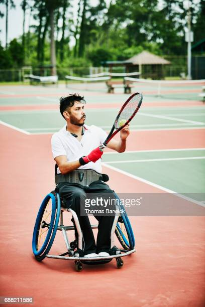 Adaptive athlete preparing to serve while playing wheelchair tennis