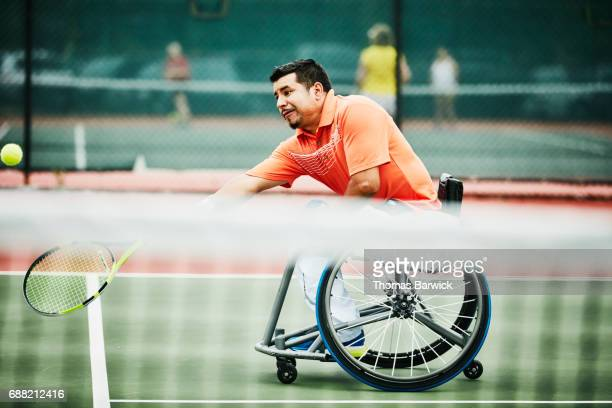 Adaptive athlete stretching for forehand shot during wheelchair tennis match