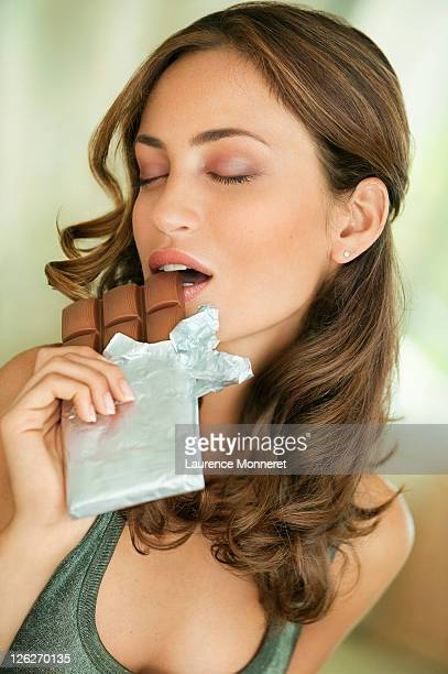 Addict woman biting milk chocolate bar