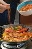 Adding chilli powder to chicken with onions and peppers, close up