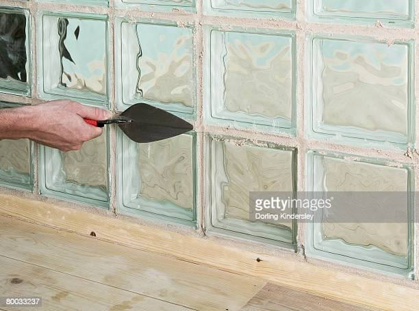 Adding grout to joints around a glass block with a trowel