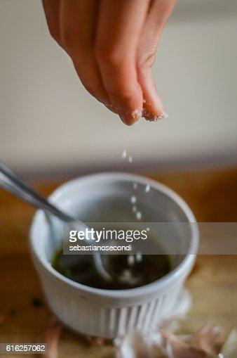 Adding salt to condiment sauce : Stock Photo