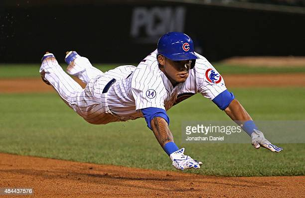 Addison Russell of the Chicago Cubs dives into third base with a triple in the 5th inning against the Detroit Tigers at Wrigley Field on August 18...