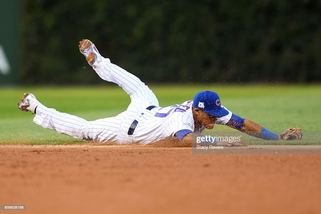 Addison Russell #27 of the Chicago Cubs dives to field a ground ball in the seventh inning against the Washington Nationals during game three of the National League Division Series at Wrigley Field on October 9, 2017 in Chicago, Illinois.